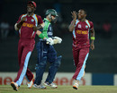Fidel Edwards and Darren Sammy celebrate after William Porterfield's wicket