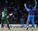 MS Dhoni tosses the ball in the air after taking the catch of Kamran Akmal