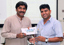 Javed Miandad presents a cash award and trophy to umpire Ahsan Raza