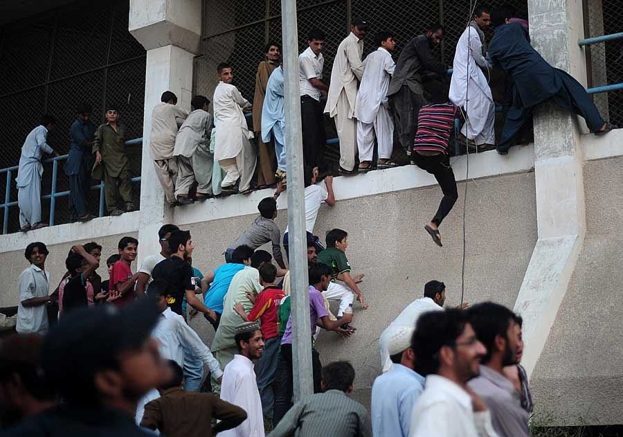 Fans try to climb their way into the National Stadium in Karachi