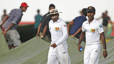 Mahela Jayawardene and Nuwan Kulasekara go off the field as the covers come on