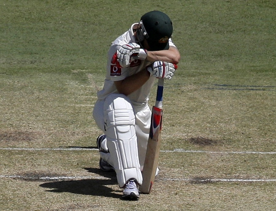 Matthew Wade kneels over his bat after he was bowled