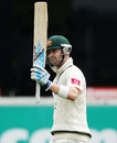 Michael Clarke raises his bat after reaching a half-century