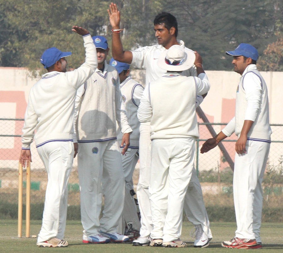 Pankaj Singh celebrates one of his five wickets with his teammates