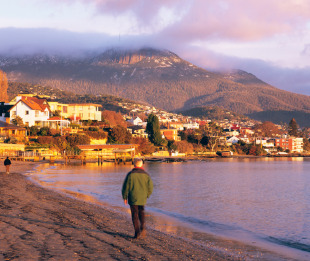 A man walks along the bank of the Derwent river in Hobart, Tasmania,