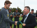 Kane Richardson is handed his Australia cap by Rod Marsh