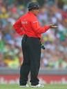 Umpire Marais Erasmus judges the rainfall before play is halted