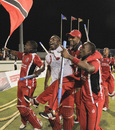 Kieron Pollard and Dwayne Bravo lift their captain Denesh Ramdin
