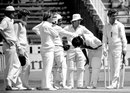 England players gather round Iqbal Qasim after he was struck by a Bob Willis bouncer