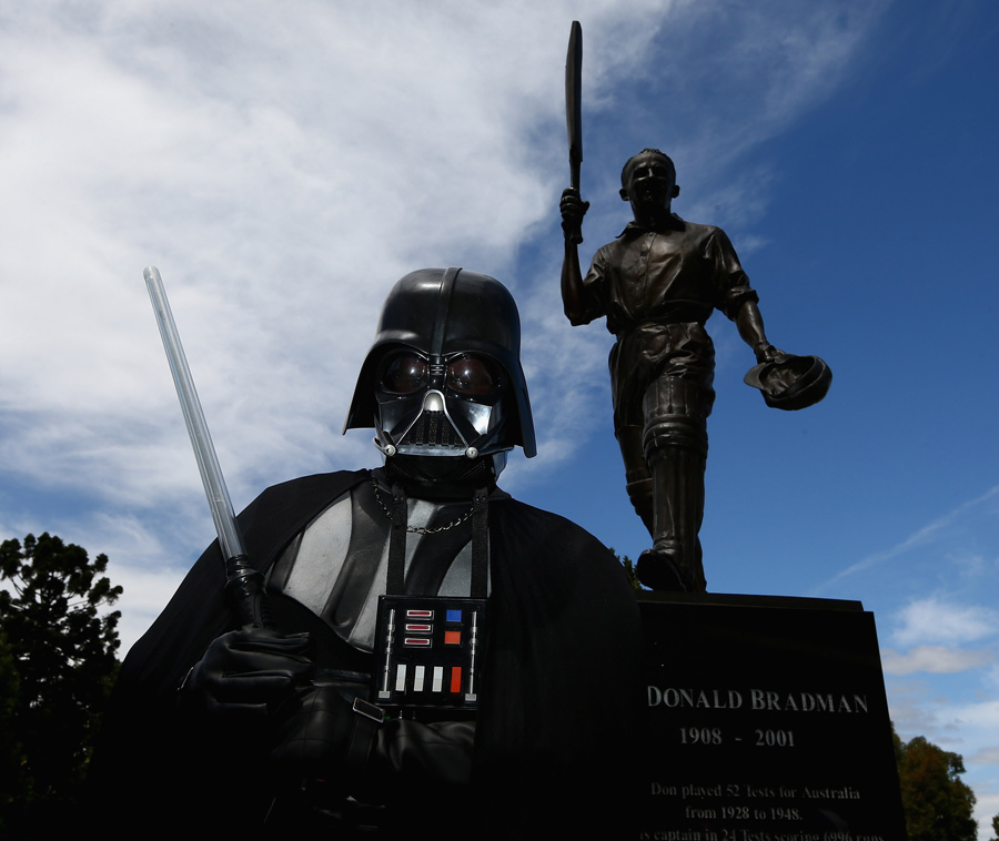 A fan dressed as Darth Vader poses in front of a Don Bradman statue