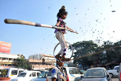A young street performer balances on a tightrope as her mother beats a drum