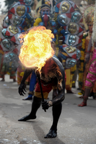 An artist performs with fire during the final procession of the eleven-day traditional festival of Bonalu, Hyderabad, July 16, 2012