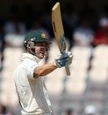 Michael Clarke raises his bat after reaching fifty