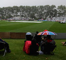 Spectators take cover as rain falls at University Oval, New Zealand v England, 1st Test, Dunedin, 1st day, March, 6, 2013