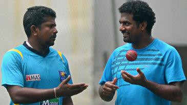 Rangana Herath talks to former cricketer Muttiah Muralitharan during a practice session