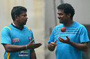 Rangana Herath talks to former cricketer Muttiah Muralitharan during a practice session