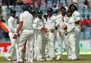 India players wait for Mitchell Johnson to leave after he was bowled