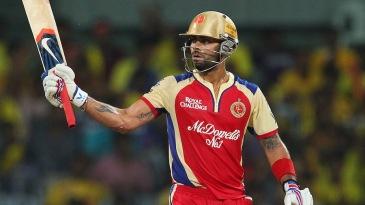 Virat Kohli raises his bat after completing his half-century