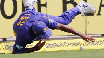 Chaminda Vaas dives in an attempt to save a boundary