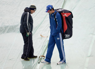 Alastair Cook inspects the covers on the square as rain abandoned the opening day of the second Test at Headingley