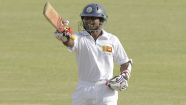 Kaushal Silva raises his bat after scoring a hundred