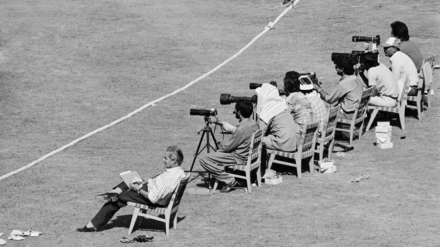 John Woodcock sits next to photographers behind the boundary