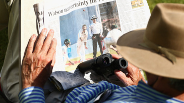 A spectator reads a newspaper