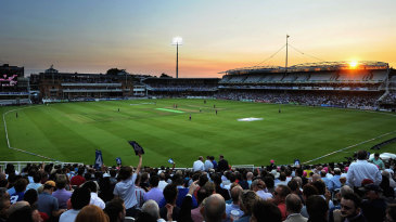 A packed crowd salutes a boundary as the sun sets