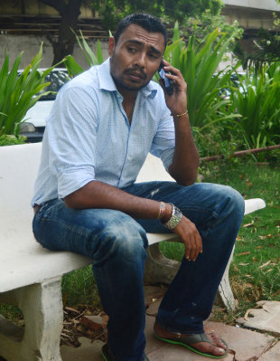 Danish Kaneria on the phone outside his apartment, Karachi, July 5, 2013
