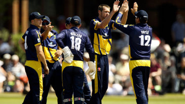 Michael Hogan gets a high five for one of his three wickets