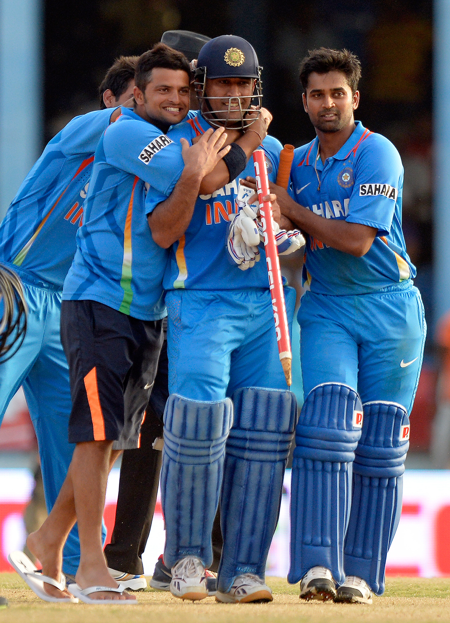 MS Dhoni is surrounded by his team-mates after lifting India to victory