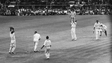 Richie Benaud bowls Peter May around his legs at Old Trafford