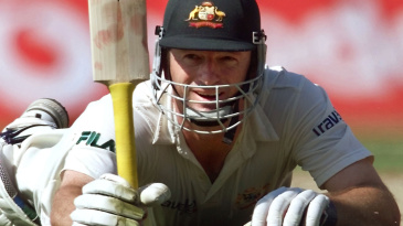 Steve Waugh raises his bat after reaching his hundred on an injured leg