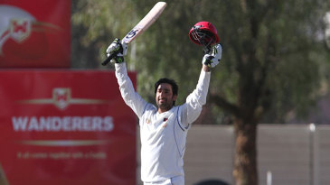 Asghar Stanikzai raises his bat after reaching his century