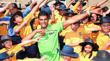 Gurinder Sandhu does the 'lightning Bolt' pose with kids at a Cricket Australia community event