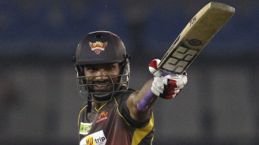 Shikhar Dhawan raises the bat after reaching his fifty