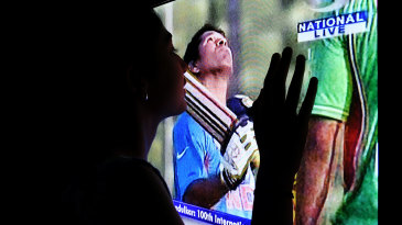 A fan watches Sachin Tendulkar on television