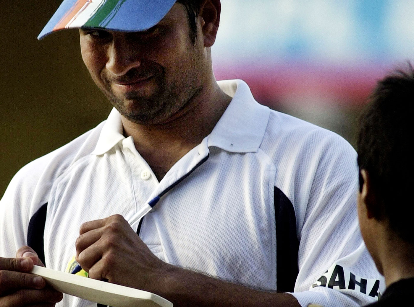 Sachin Tendulkar smiles while signing an autograph for a young fan