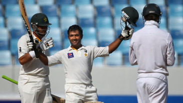 Asad Shafiq raises his bat after reaching his century