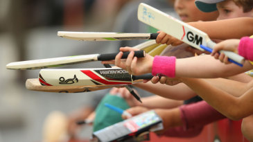 Fans line up bats for autographs on the sidelines of the Ryobi final