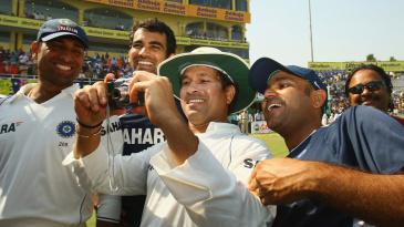 Sachin Tendulkar takes photos after the victory