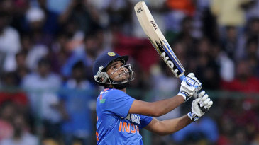 Rohit Sharma watches the ball soar into the evening sky