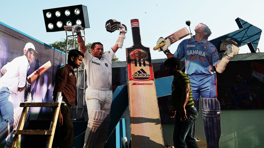 Workers place cut-outs of Sachin Tendulkar on a float in Kolkata