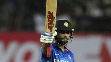 Virat Kohli raises the bat after reaching his fifty