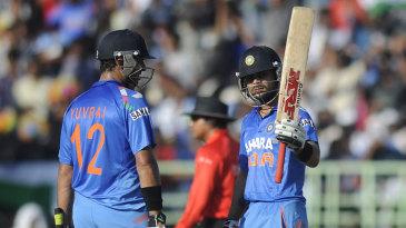 Virat Kohli raises the bat after scoring fifty