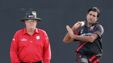 Tanwir Afzal coming in to bowl against Ireland along side umpire Derek Walker