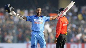 Shikhar Dhawan raises the bat after reaching his century