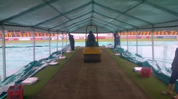 Groundsmen work on the pitch before the tour match