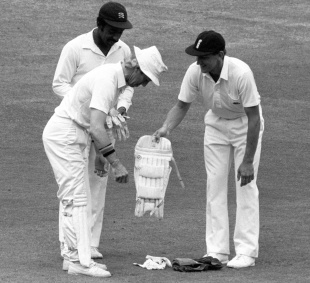 A relieved Bill Athey helps Taylor put on the keeping pads while Roland Butcher holds the gloves, Lord's, 1986