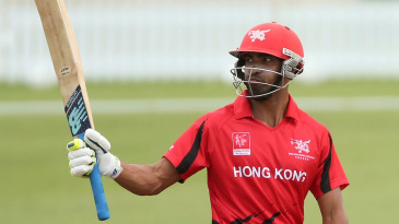 Irfan Ahmed raises his bat after reaching his fifty